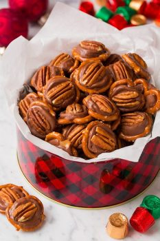 Pretzel Turtles in a Christmas tin with tissue paper. Made with pretzels, rolo candy and pecans.